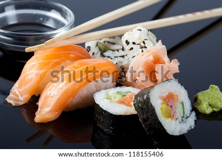 Sushi with salmon, and chopsticks, with a black background