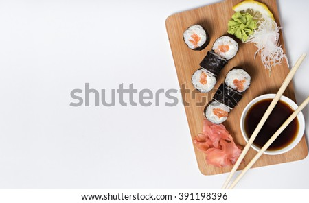 sushi with salmon served on wooden plate - stock photo