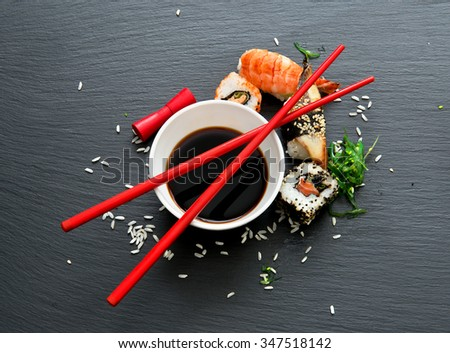 Sushi with soy in saucers on a slate table - stock photo