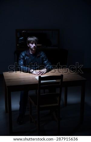Suspect man sitting alone in interrogation room - stock photo