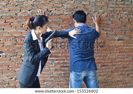 Suspect under arrest by policewoman. - stock photo