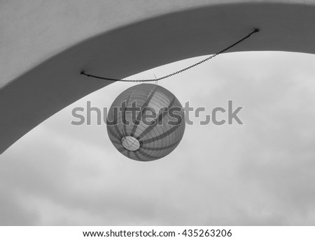 Suspended Chinese paper lantern swaying in the wind in black and white