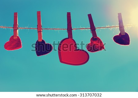 suspended heart shape items hanging from a twine line with the sky and sun in the background with a toned instagram filter - stock photo
