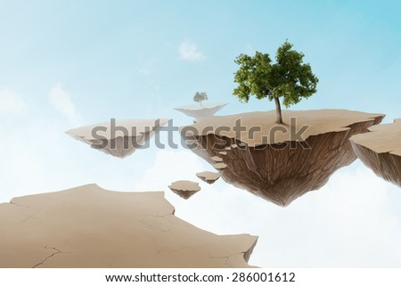 Suspended lands with a tree for environmental concept - stock photo