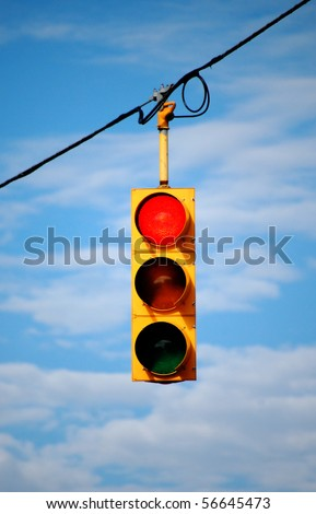 Suspended stoplight showing red with sky background - stock photo