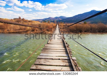 Suspended wooden bridge over a river - stock photo