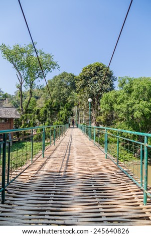 Suspension bamboo bridge across the river in a forest - stock photo
