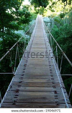 Suspension bridge leading to the bright side - stock photo