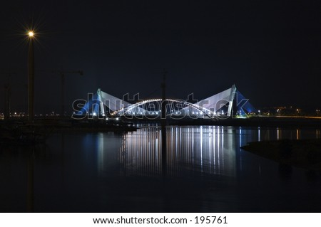 Suspension bridge lit up at night, with its reflection on the lake