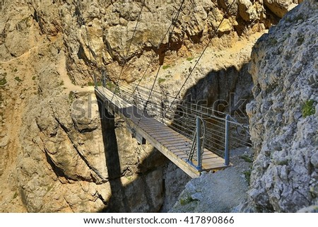 Suspension bridge on an alpine route - stock photo