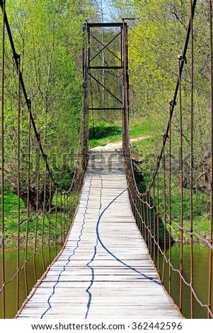 Suspension bridge to the other shore of the river - stock photo