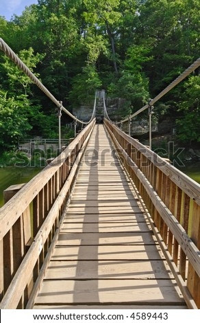 Suspension cable foot bridge on a hiking trail, water below - stock photo