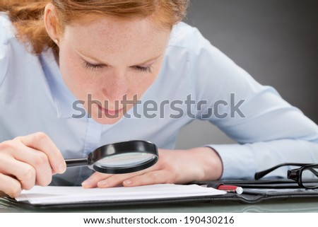 Suspicious business leader analyzing the small print of a document or contract with a magnifier. - stock photo