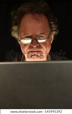 Suspicious older Man on Computer/Mature Man Computer/Man is looking at his computer for emails and internet - stock photo
