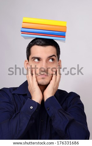 Suspicious student holding a pile of books on his head raising his eyebrow. Funny teacher with colorful books over his head looking to the side wondering.