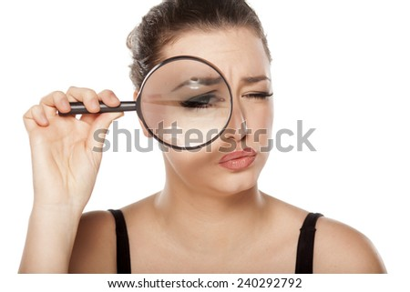 suspicious young woman looking through a magnifying glass - stock photo