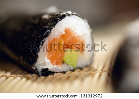 Susshi roll with salmon and avocado. Beautiful macro with shallow dof. - stock photo
