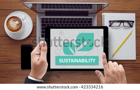 SUSTAINABILITY, on the tablet pc screen held by businessman hands - online, top view - stock photo