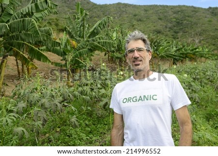 Sustainable agriculture: Organic farmer in front of farmland - stock photo
