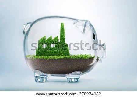 Sustainable investment concept with grass growing in shape of factory inside transparent piggy bank
