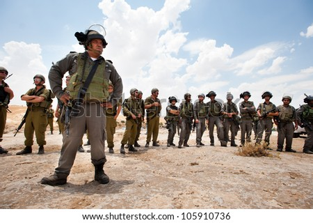 SUSYA, OCCUPIED PALESTINIAN TERRITORIES - JUNE 22: Israeli soldiers stand guard during a demonstration near the Palestinian village of Susya, West Bank, June 22, 2012. - stock photo