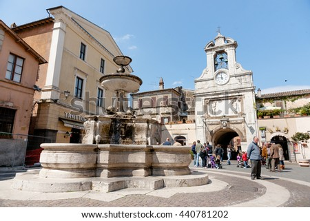 SUTRI, ITALY - APRIL 17; Small Italian village square with people gathering and traditional fountain clock tower and arched entry in historic Mediterranean town. on April 17, 2011 in Sutri, Italy. - stock photo