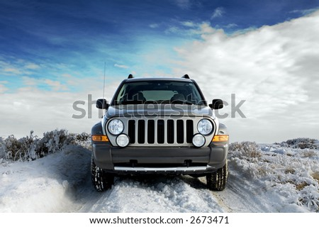 SUV on a rural snowy frosted road, winter sky background - stock photo