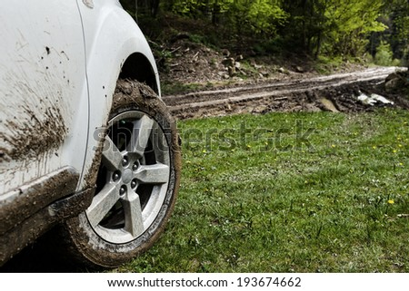 SUV wheel closeup in a countryside landscape with a muddy road and grass - stock photo