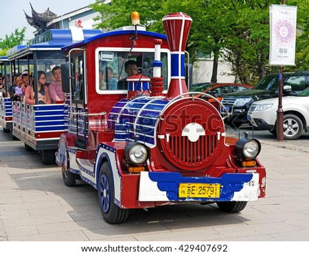 SUZHOU, CHINA - April 17, 2016: A small sightseeing tourist train in Suzhou. Founded in 514 BC, Suzhou has over 2,500 years of history, with an abundant display of relics and sites of interest. - stock photo