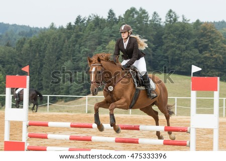 "SVEBOHOV, CZECH REPUBLIC - AUG 20: Beautiful blond horsewoman during the jump on a horse. The height of obstacles is 80 cm.  ""HobbyJumping Event  2016"" on August 20, 2016  in Svebohov, Czech Republic."