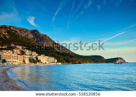 Sveti Stefan sand beach and town view near Budva, Montenegro. Balkans, Adriatic sea, Europe. Sunset time