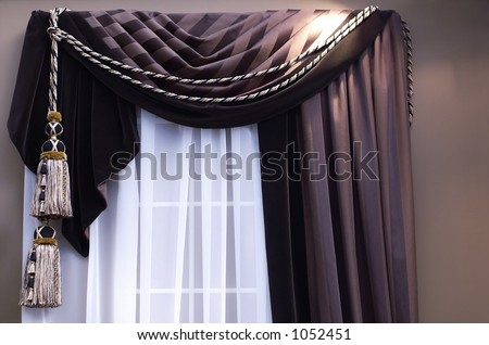 swag curtains with tassles on window with sheers