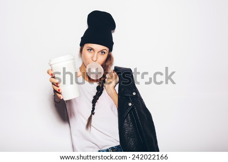 swag girl in black beanie giving cup of coffee and inflating bubble of chewing gum. Modern fashion girl.  White background, not isolated, not isolated - stock photo