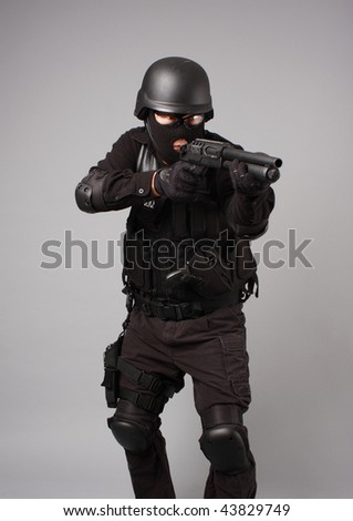 SWAT police officer aiming a shotgun.