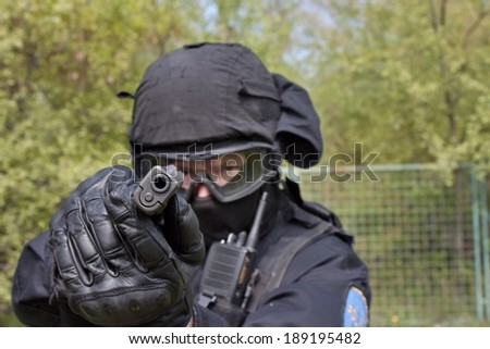 swat police officer pointing a gun at the camera, close-up - stock photo