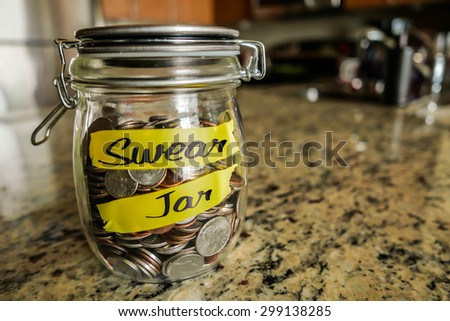 "Swear Jar. A clear glass jar filed with coins and bills, saving money. The words ""Swear Jar"" written on the outside."