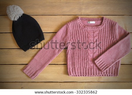 sweater and hat for baby girl on wooden background