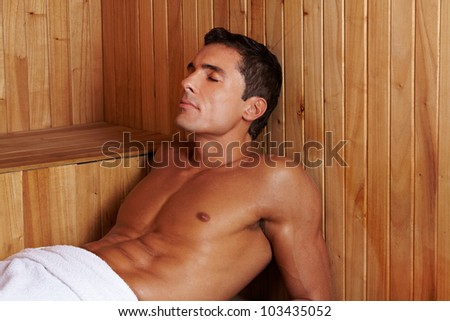 Sweating attractive man laying in a sauna - stock photo