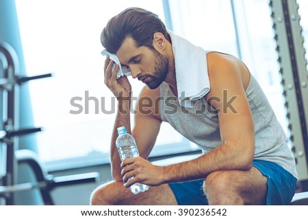 Sweaty after great work out. Handsome young men in sportswear whipping sweat with his towel and holding water bottle while sitting at gym - stock photo