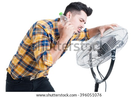 Sweaty and thirsty man standing near fan and cooling off on hot summer days isolated on white background - stock photo