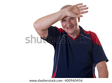 Sweaty elderly man with shaved head and wearing blue shirt wipes forehead and smiles