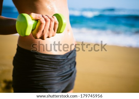 Sweaty fitness woman working out with dumbbells in summer on beach. - stock photo