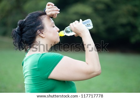 Sweaty overweight woman drinking water after a long run. Selective focus.