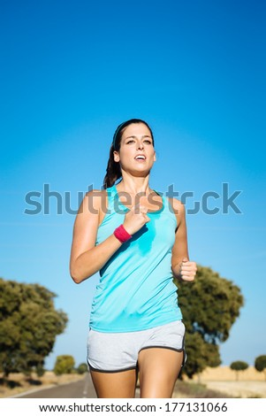 Sweaty woman running on road. Fit girl training and exercising hard. - stock photo