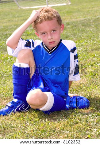 Sweaty young boy sitting on grassy soccer field resting at halftime - stock photo