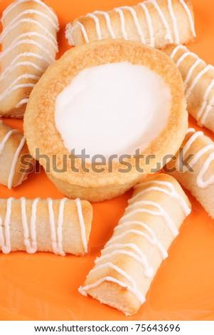 Swedish almond tart and danish macaroon fingers on a orange plate ...
