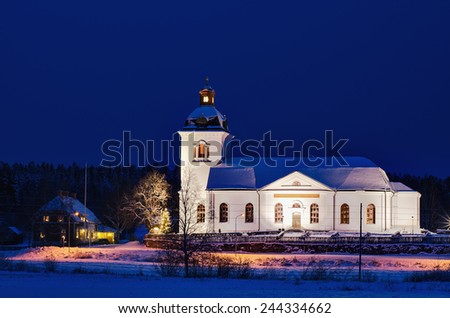 Swedish church building, illuminated at night with deep blue sky - stock photo