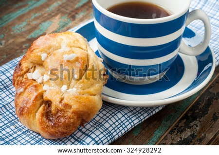 Swedish cinnamon berry bun served on a rustic wooden table with a cup of freshly brewed coffee in a blue and white striped cup and saucer. Coffee and a bun is a tradition in Sweden known as fika. - stock photo