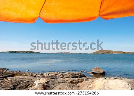 Swedish Coastline Bohuslan Archipelago Close To Gothenburg Swedish West Coast With Rocks And Cliffs Beautiful Beach With Orange Parasol With Ocean And Sea Sunny Weather With Blue Sky - stock photo