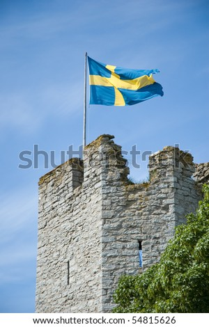 Swedish flag above medieval wall on Gotland - stock photo
